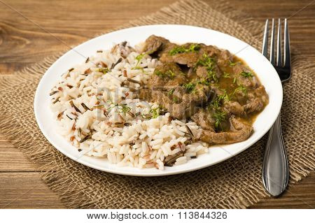 Stewed beef and rice on the white plate on wooden background.