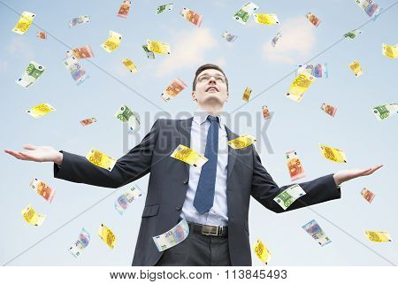 Happy businessman standing in the rain of  money