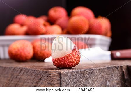 Lychee Fruit, Which Is Called Chinese Plum, Is On The Dark Board And In Basket.