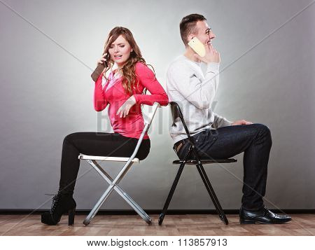 Young Couple Talking On Mobile Phones.