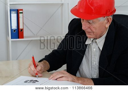 Mature Architect With Red Helemet Writing