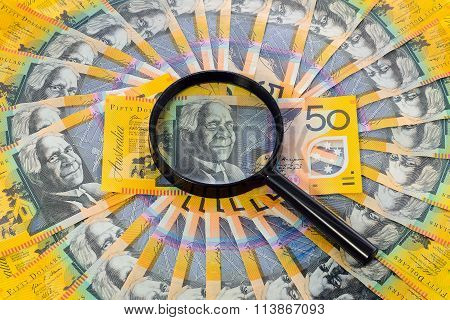 Australian Banknote Under A Magnifying Glass Is Being Inspected
