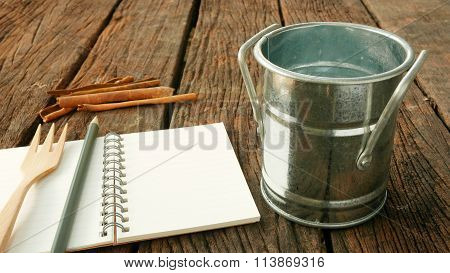The small vintage zinc pot and cinnamon with blank earth tone note book