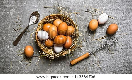 Basket With Eggs, With A Whisk . On Stone Background.