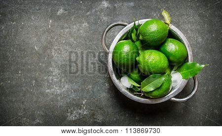 Lime Background. Fresh Limes In A Saucepan With The Leaves .