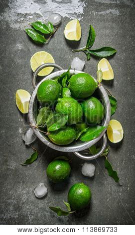 Lime Background. Fresh Limes In A Saucepan With Slices And Leaves Around.