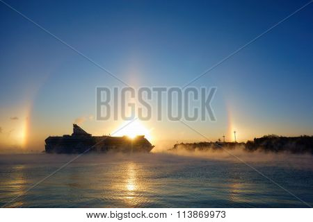 Ferry arriving to Helsinki harbor on a cold morning with winter halo on background