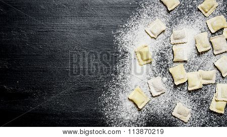 Homemade Ravioli With Flour. On Black Table With Flour.