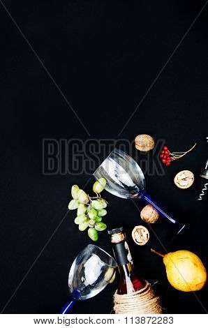 The still life with white wine in glass bottle on black background. Glasses of wine with fresh grape