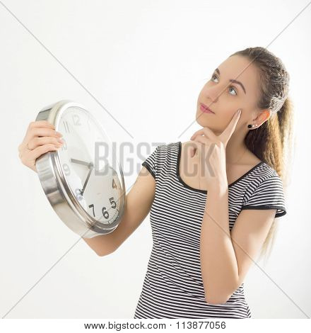 Beautiful young woman looking at a large silver retro clock that she is holding, she wonders how muc