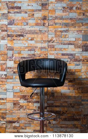 Black leather armchair against colorful brick wall interior