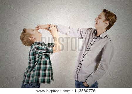 Two caucasian teen boys quarrel isolated on gray background. Concept of emotions.