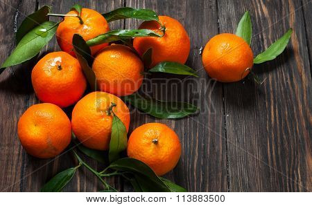 Clementine mandarines with leaves on dark wooden background