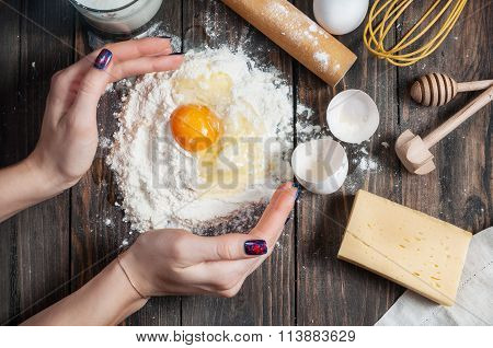 Female baker cooking dough with eggs, butter and milk