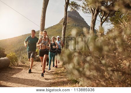 Group Of Fit People Trail Running On A Mountain Path
