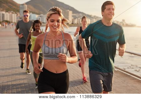 Fit Young Woman Running With Friends