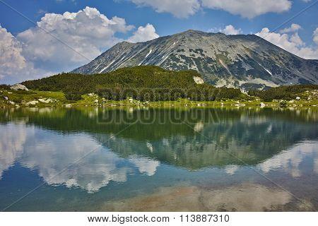 Clouds over Todorka Peak and reflection in Muratovo lake, Pirin Mountain