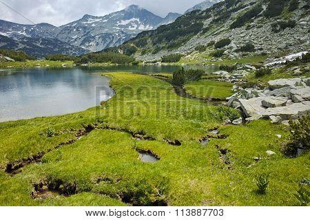 Banderishki Chukar peak and reflection in Muratovo lake Before storm, Pirin Mountain