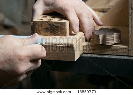 Hands male sandpaper grinds wood product in one studio