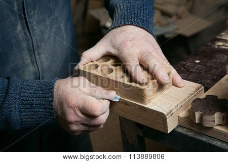 Hands male sandpaper grinds wood product in studio