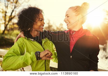 Two Smiling Sportswomen Hugging While Standing Outdoors