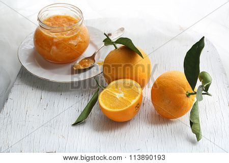 Orange Confiture In A Glass Jar And Fresh Oranges