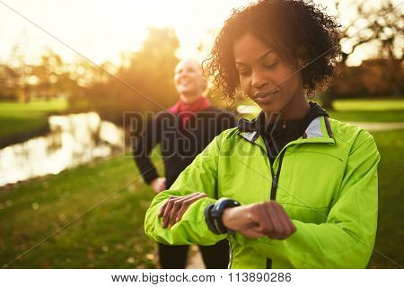 Young Female Athlete Looking At Her Watch