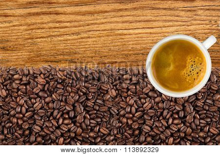 Close-up Of Roasted Coffee Beans And Cup Coffee Over Wooden Background