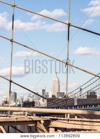NEW YORK USA - JANUARY 5 2015: The Empire State Building shines in the afternoon seen from the Brooklyn Bridge. The Empire State Building is a 102-story landmark in New York.