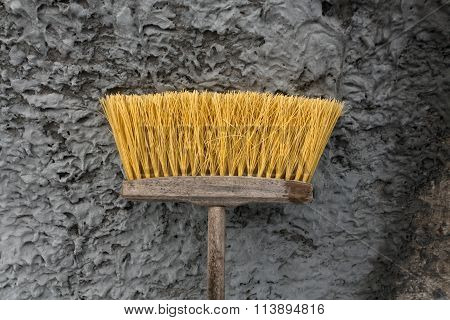 House And Street Cleaning Yellow Brush In Front Of Wall.