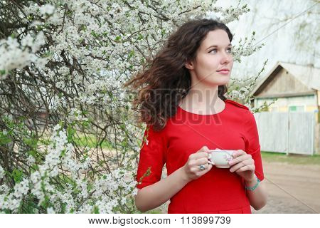 Young beautiful brunette girl with tea cup in arm standing in spring flowering garden