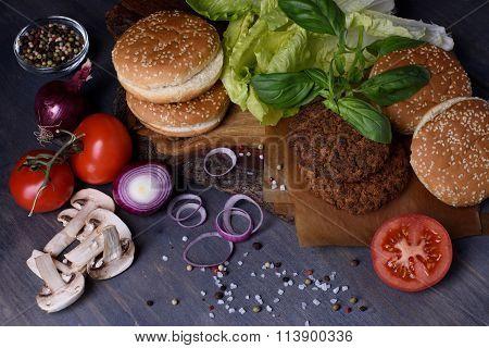 Burger ingredients: beef patties, sesame bun, fresh vegetables, pepper, mushrooms over wooden table.
