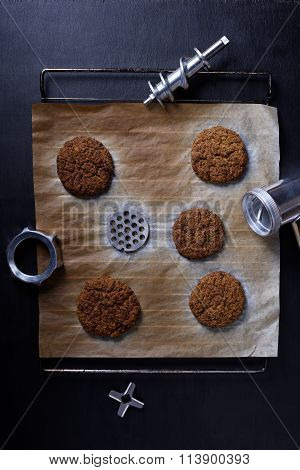 Prepared ground beef patties or cutlets on a baking tray with steal grinder parts, dark background.