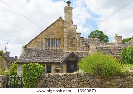 old traditional english stone cottage with stone wall and wooden gate