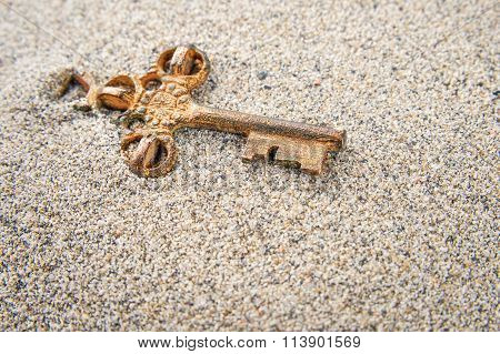 Old key in the sand