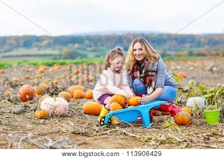 Little kid girl and mother having fun on pumkin field