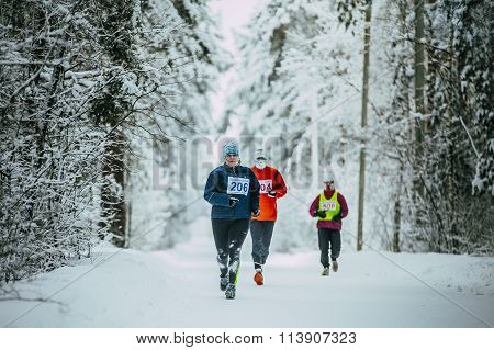 woman middle-aged athlete running down alley Park in snow. weather is cold