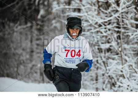 elderly athlete runner is running through snowy woods. cold weather frost on his mustache