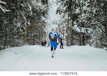 General plan winter forest and young athlete running in cold weather