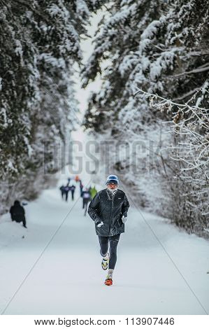 elderly athlete running in winter woods in cold weather of alley in forest