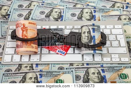 Steel Handcuffs, Credit Card And Rolls Of Russian Rubles And Dollars Lying On A Computer Keyboard On