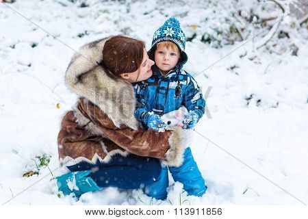 Happy child and mother having fun with snow in winter