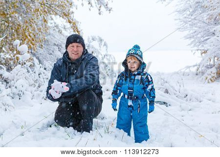 Happy son and father having fun with snow in winter