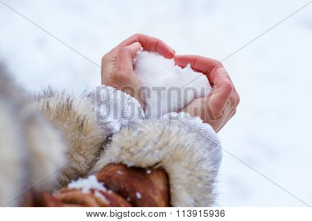 Hands of woman with snow heart