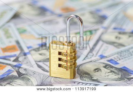 Yellow opened padlock and dollars (DOF shallow)