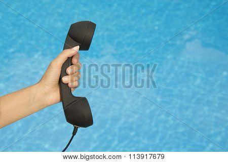 Hand holding retro landline telephone receiver