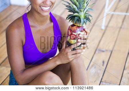 Healthy concept. Woman holding a mason jar filled with tropical fruits looking like a pineapple