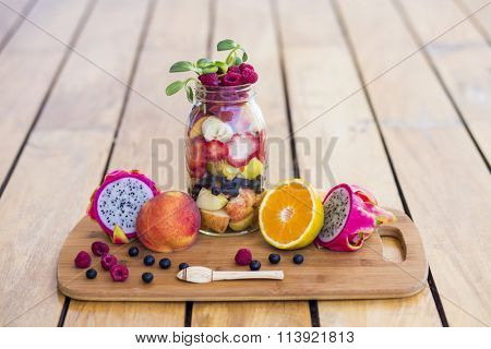 Mason Jar full with tropical fruits, topped with sunflower sprouts in a wooden surface