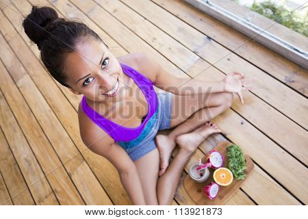 Woman in meditation posture shot from above, with a healthy place of fruits