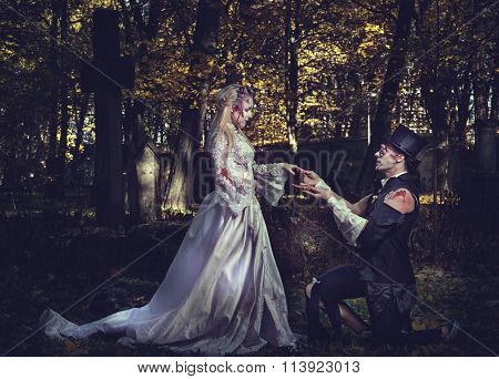Dressed in wedding clothes romantic zombie man makes a proposal of betrothal to his zombie girlfriend.